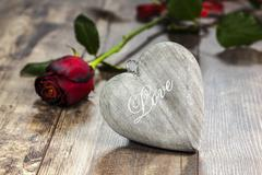 love symbol. heart on a wooden background with red rose. - stock photo