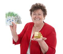 isolated senior woman with money: concept for pension and heritage. - stock photo