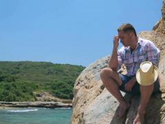Sad man sitting alone on rocks next to the sea Stock Footage
