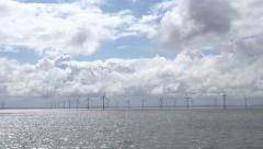 Zoom out, wind turbine farm in irish sea in liverpool bay, england, uk Stock Footage