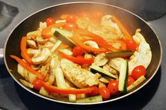 Cooking chicken and vegetables Stock Photos
