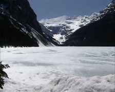 Lake Louise in Rocky Mountains scenery - pan frozen glacial lake + snow pile Stock Footage