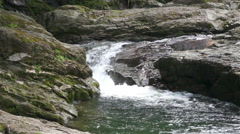 Water flows between the rocks in the mountains Stock Footage