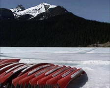 Canoes on the bank of  frozen glacial lake + pan Chateau Lake Louise Stock Footage