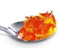 Spoon full of orange jelly Stock Photos