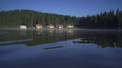 Group of small colored houses among huge pine trees and lake Stock Footage
