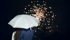 People stand under an umbrella and watch fireworks. Stock Footage