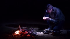 Man Camping And Eating Cooked Bugs By The Fire - stock footage