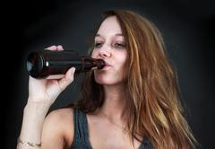 Drunk woman drinking beer over black Stock Photos