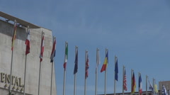 National flags waving in the wind, hoisted outside international hotel, vacation Stock Footage