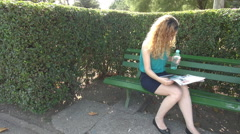 Blonde woman in park, reading newspaper in weekend mornings, drinking cold water Stock Footage