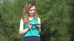 Beautiful blonde curly hair little girl outside, send message from smartphone Stock Footage