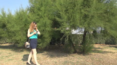 Young pretty woman in the park online communication on smart phone, anxious walk Stock Footage
