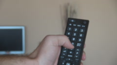 Close up man hand with remote controller, pushing the buttons, changing channels Stock Footage