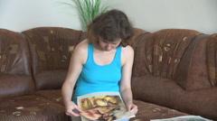 Woman faddist looking at paintings on canvas, handmade arras sewed, hobbyist Stock Footage