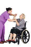 nurse assaulting senior woman in wheelchair - stock photo