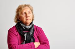 senior woman in pink with crossed arms - stock photo
