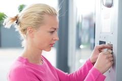 Woman inserting coin in the vending machine. - stock photo