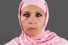 Middle aged muslim in pink scarf Stock Photos