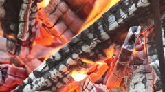 Close up of burning logs at bonfire, beautiful flames and smoke from firewood - stock footage