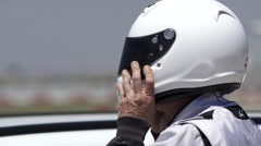 Race car driver wears helmet and enters car Stock Footage