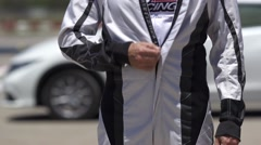 Race car driver zipping his suit - stock footage