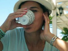 Woman drinking coffee and smiling to the camera in street cafe Stock Footage