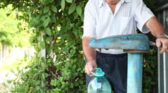 Old man pumping water, well, fill a plastic bottle, hydration, rural,countryside - stock footage