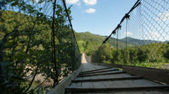 DOLLY MOTION: Suspension Bridge over the River highlands. Ukraine, Carpathians. - stock footage