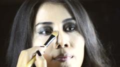 Contour Makeup, Asian woman applying make up to her face. Close up. - stock footage