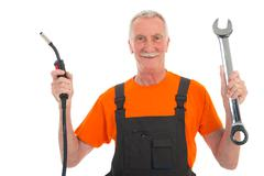 Happy man in orange and gray overall with wrench Stock Photos