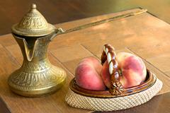 Old brass arabian style coffee pot and ceramic vase with peaches. Stock Photos
