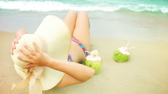 Woman drink coconut on a beach. - stock footage