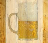 Translucent beer glass on a wooden abstract background. Stock Photos