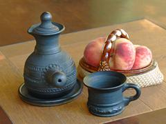 Arabian style coffee pot and ceramic vase with peaches. Stock Photos