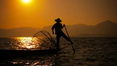 Fisherman with a trap on a boat during sunset. inle lake, myanmar Stock Footage
