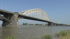 Large barge passes under the Nijmegen road bridge, Nijmegen, Netherlands. Stock Footage