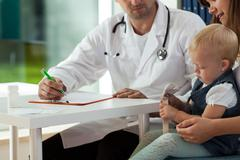 Mother with daughter on medical appointment Stock Photos