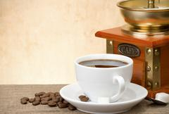 cup of coffee with beans and grinder - stock photo