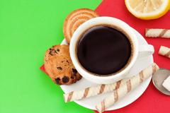 Cup of coffee and cookies on green Stock Photos