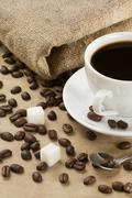 cup of coffee and beans at sacking - stock photo