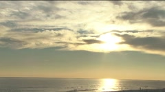 Beach with sun reflecting thru clouds Stock Footage