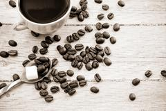 beans and cup of coffee on wood board - stock photo
