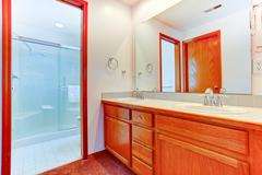 Bright bathroom with glass door shower and vanity cabinet Stock Photos