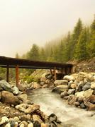 Wooden bridge over Alps rapids on mountain torrent in Alps, big boulders Stock Photos