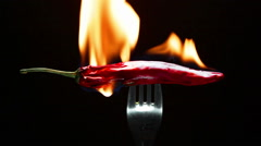 Burning red chili pepper on a fork Stock Footage