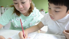 Asian Mom is painting her son to do homework Stock Footage