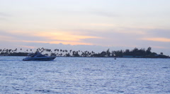 Powerboat yacht tropical sunset island in background Stock Footage