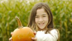 Pre-Teen Asian Girl Holds Up A Pumpkin And Laughs And Hugs Her Pumpkin Tight - stock footage