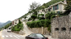 Traffic on the street through the coastal town. Luxury villa on the hilly coast. Stock Footage
